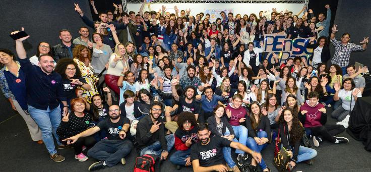 Na imagem, todos os participantes do Demoday, entre alunos, educadores, familiares e organizadores, aparecem de braços abertos, em volta de um totem com logo do programa Pense Grande