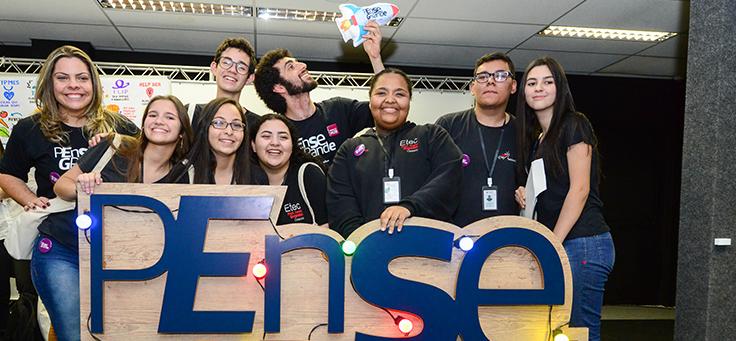 Na imagem, nove integrantes do Women Work, grupo vencedor do Demoday 2018, posam em volta de totem do programa Pense Grande