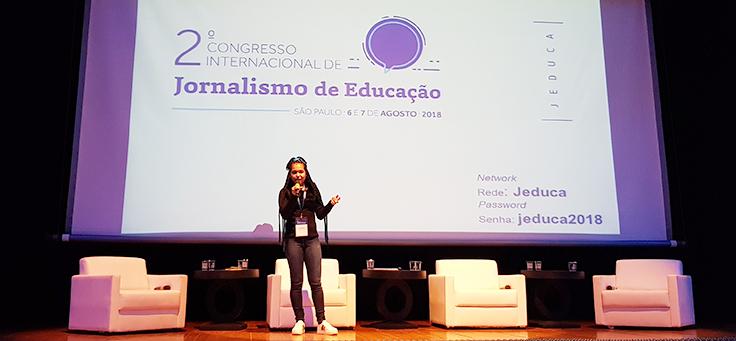 A aluna Aniely Silva está em pé no palco do Jeduca. Ela usa cabelos compridos e trançados e está com microfone na mão.