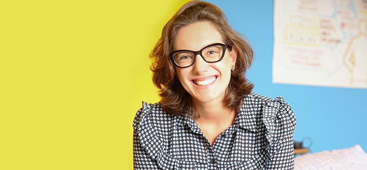Tonia Casarin, especialista em competências socioemocionais, está sorrindo na imagem. Ela usa óculos e blusa estampada, em preto e branco.
