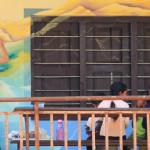 Pessoa de costas pinta parede em escola durante viagem de volunturismo