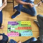 Na imagem, grupo com quatro jovens está sentado em torno do tabuleiro do jogo Se Vira, que fortalece a cultura empreendedora