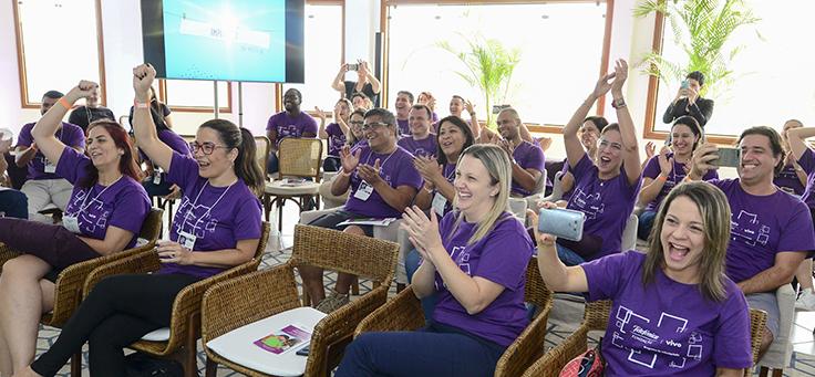Na imagem, colaboradores do programa de voluntariado usam camiseta púrpura do programa. Eles estão sentados em uma plateia, aplaudindo e comemorando durante evento