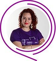 Na imagem, a voluntária Kelly Cristine Lima Fernandes posa de braços cruzados e usando camiseta púrpura do Programa de Voluntariado. Ela tem cabelos ruivos cacheados e sorri para a foto