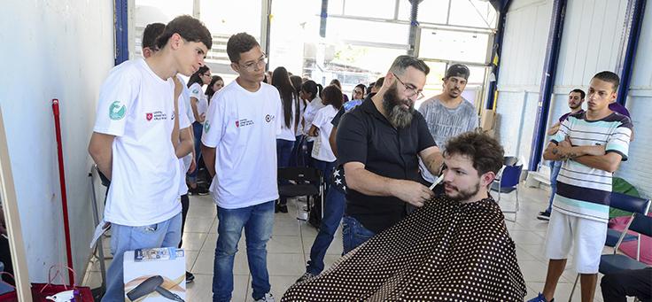 Pessoa tem cabelo cortado durante ação com trainees