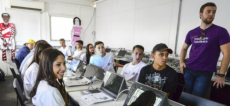 Pessoas sorriem sentadas em mesa com computadores em ação com trainees