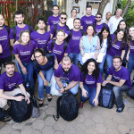 Imagem mostra pessoas usando camiseta roxa onde se lê Voluntários Telefônica em ação com trainees