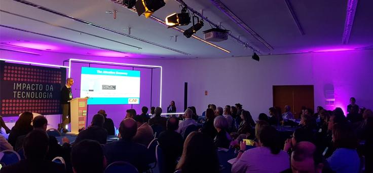 Palestrante inglês Rhodri Davies no palco do Fórum Brasileiro de Filantropia discursa para plateia.