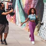 Cantora Lellezinha caminha em abertura do Pense Grande.doc; Ao seu lado, duas pessoas seguram câmeras de filmagem