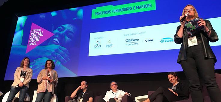 Três palestrantes estão em pé e outros três sentados no palco do festival Social Good Brasil