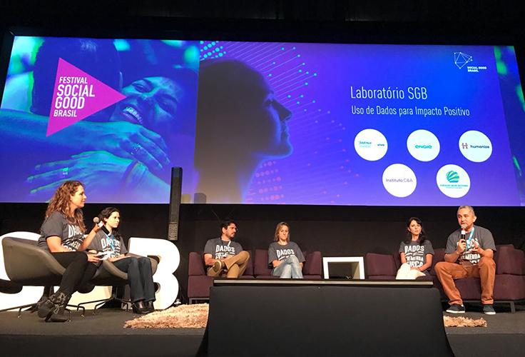 Seis palestrantes dividem palco do festival Social Good Brasil. Eles estão sentados em sofás e poltronas