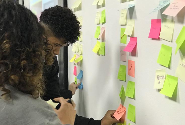 Duas mulheres colam post its na parede durante dinâmica sobre metodologia da pesquisa Juventude Conectada