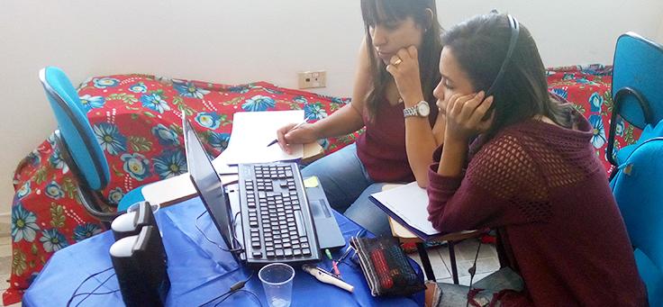 Na imagem, duas mulheres estão olhando para a tela de um notebook durante curso semipresencial. Uma delas utiliza um fone de ouvido
