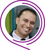 Taissir Wilkerson Carvalho sorri para a foto, ele tem cabelos curtos e usa terno e gravata