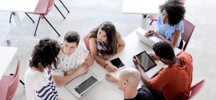 Imagem mostra jovens sentados no chão usando computadores