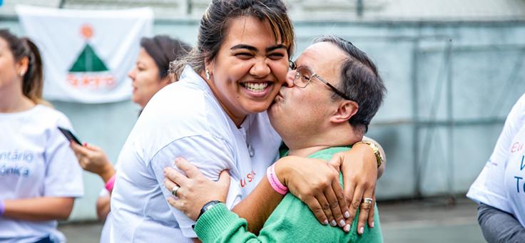 Colaborador abraça jovem em instituição durante o dia dos voluntários