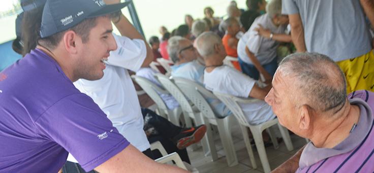 Colaborador interage com idoso durante dia dos voluntários