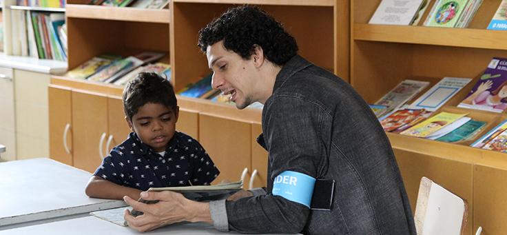 Colaborador lê livro junto com criança durante o dia dos voluntários