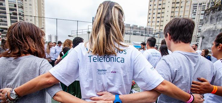Voluntário se abraçam em ciranda durante atividade do dia dos voluntários
