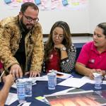 Beto Silva, que conduz oficina sobre futurismo, está em pé orientando cinco educadores sentados em uma mesa