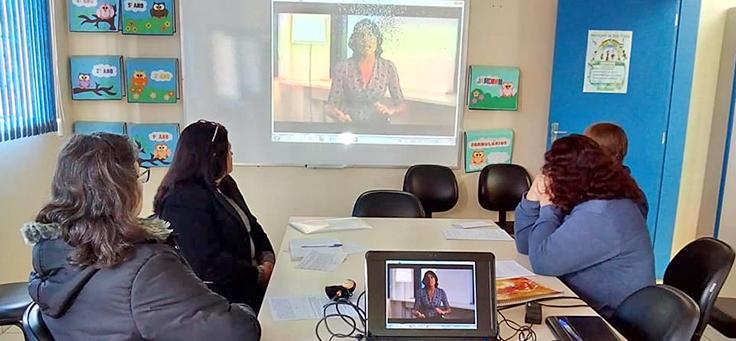 Quatro educadores sentados em volta de uma mesa na escola, assistem a uma projeção de vídeo como parte da formação do Aula Digital nas escolas de Viamão