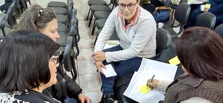 Quatro educadores reunidos em grupo fazem uma atividade como parte das formações do Aula Digital nas Escolas de Viamão
