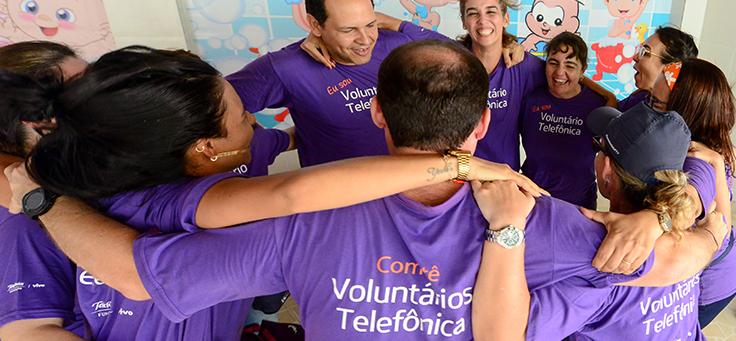 Colaboradores da Telefônica estão se abraçando, formando um círculo. Eles usam camiseta púrpura na qual se lê: Comitê Voluntários Telefônica