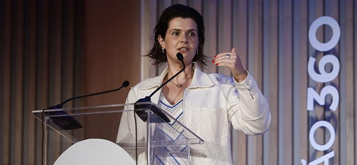 Mila Gonçalves, gerente de Programas Sociais, está em pé no palco do Educação 360