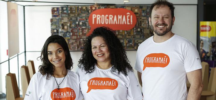 Três facilitadores do Programaê posam com camisetas do programa em estande do Educação 360