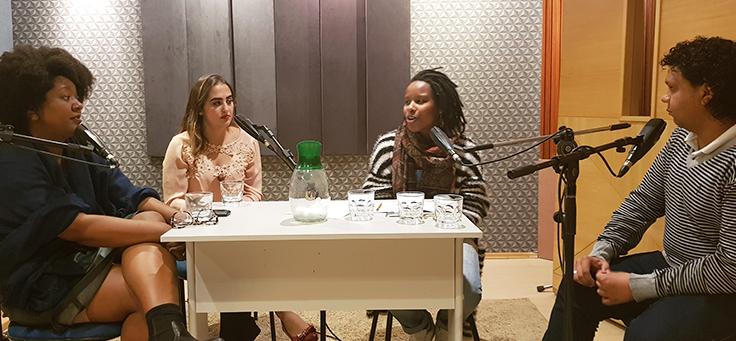 Quatro jovens conversam dentro de um estúdio de gravação
