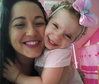 Paloma Almeida em cabelos compridos e usa batom rosa. Ela está abraçada à filha, Giovanna, que tem 3 anos e usa um laço rosa na cabeça. As duas sorriem para a foto