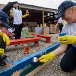 Três voluntários pintam área de recreação em uma instituição, durante o Dia dos Voluntariados