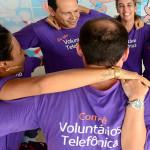 Colaboradores da Telefônica estão se abraçando em círculos. Eles usam camiseta púrpura na qual pode ler: Comitê Voluntários Telefônica