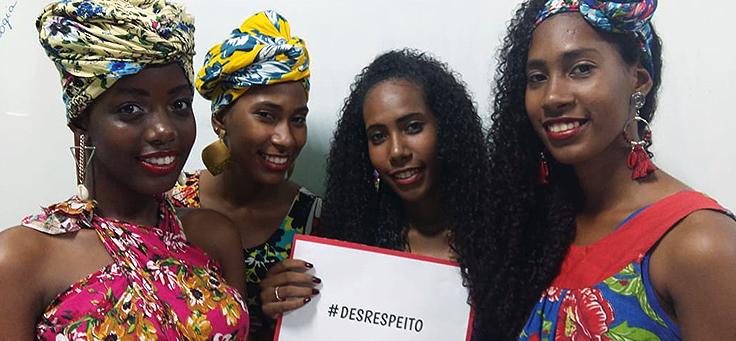 Quatro alunas negras estão posando para foto. Três delas vestem turbantes na cabeça e uma segura uma placa com a hashtag desrespeito, durante a Mostra Consciência Étnica