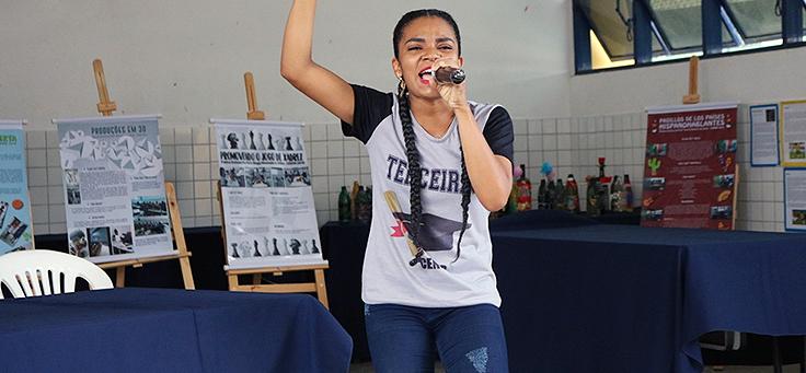 Aluna discursa ao microfone durante a Mostra Consciência Étnica