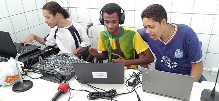 Três alunos estão sentados lado a lado. Um deles mexe em aparelho de mixagem de som e dois estão usando computador, durante a Mostra Consciência Étnica