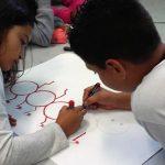 Na imagem, duas crianças estão desenhando na mesma folha de papel, em atividade ligada à Educação Socioemocional
