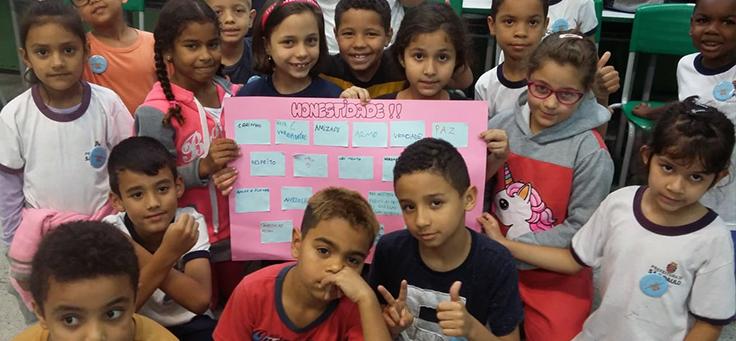 Na imagem, quatro crianças estão reunidas em torna de uma folha de papel e olhando para a câmera, em atividade ligada à Educação Socioemocional