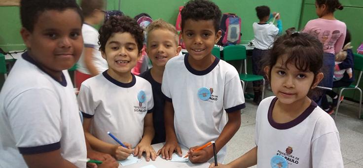 Na imagem, um grupo de crianças olha para a câmera e segura cartaz em em atividade ligada à Educação Socioemocional