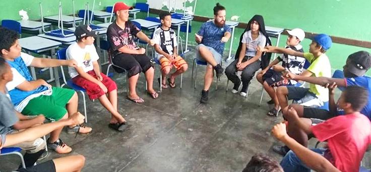 Alunos e professor estão sentados em roda em atividade promovida pelo Quero na Escola