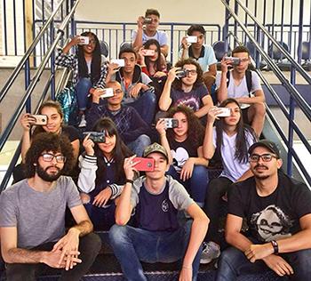 Alunos seguram smartphones em frente ao rosto e estão sentados nos degraus de um escada, ao lado de voluntários do Quero na Escola