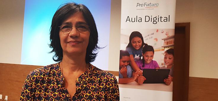 Beatriz Goulart posa para foto ao lado do banner do projeto Aula Digital