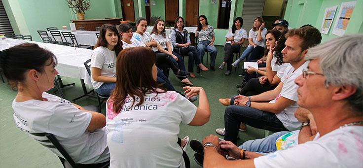 Imagens mostra voluntários sentados em roda na Escola Primavera