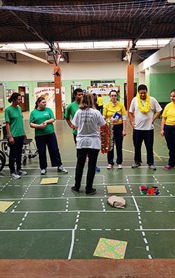 Voluntários participam de atividade na quadra de escola.
