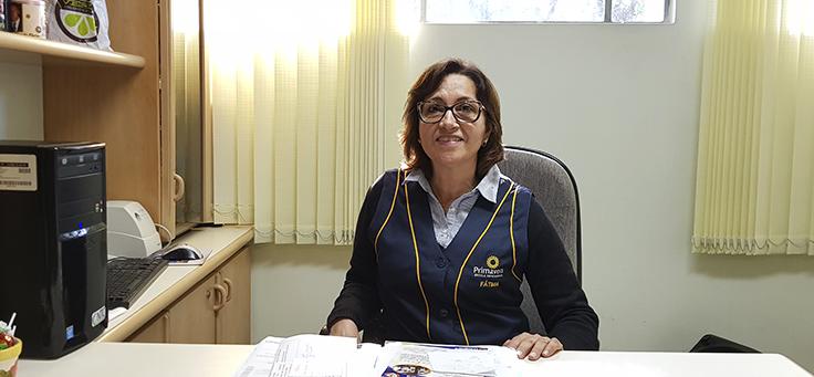 Sentada atrás de uma mesa, em sua sala, a diretora Fátima sorri para a foto. Ela está com um colete azul de uniforme da escola, usa óculos e tem os cabelos curtos.