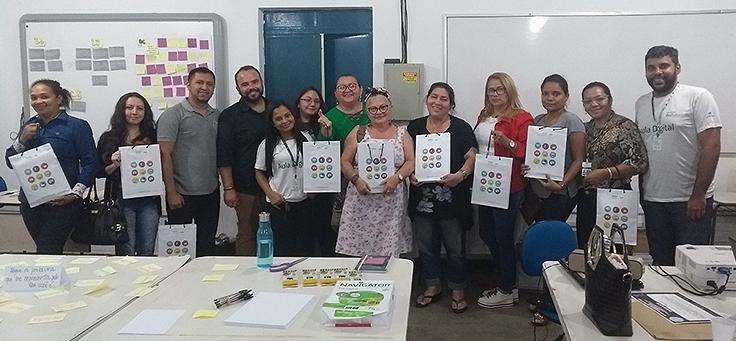 Cerca de 12 professores estão enfileirados exibindo trabalho de oficina realizada no evento Socialização de Práticas Formativas, em Manaus, que discutiu boas práticas pedagógicas.