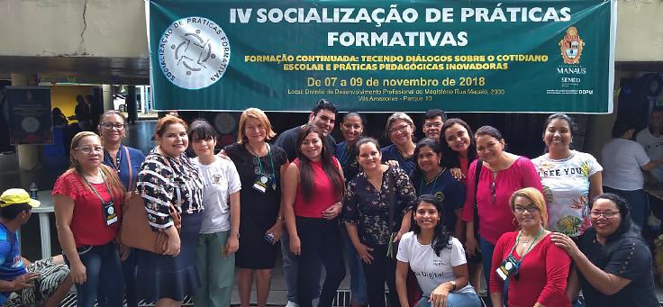 Grupo formado por cerca de 10 professores e participantes em geral posa embaixo de banner do evento de boas práticas Socialização de Práticas Formativas