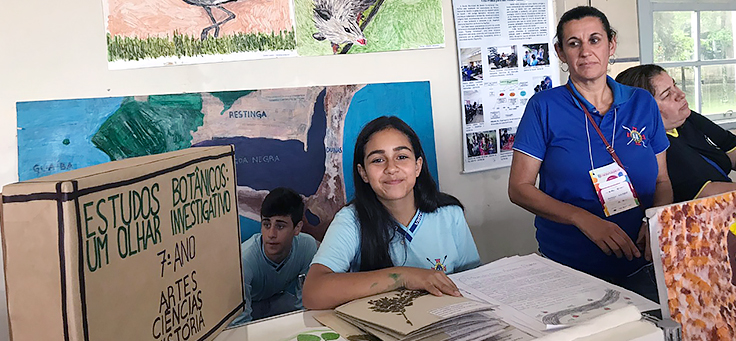 Aluna está sentada ao lado de cartaz em que se lê Estudos Botânicos, um olhar investigativo, durante atividade em mostra de boas práticas pedagógicas realizada em Viamão-RS.