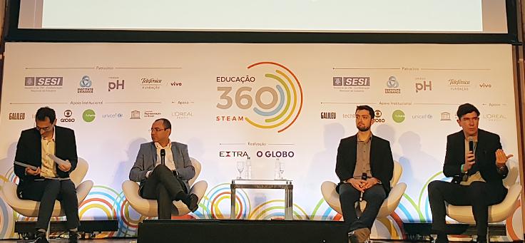 Da esquerda para a direita, Paulo Mól, diretor de operações do Sesi, fala ao microfone. Ele está sentado no palco do Educação 360 STEAM, ao lado do pesquisador Gustavo Pugliese e do professor Edson Prestes.