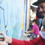 Criança usa spray para pintar mural e é observada por instrutor do Cidade na Escola, que promove a educação integral